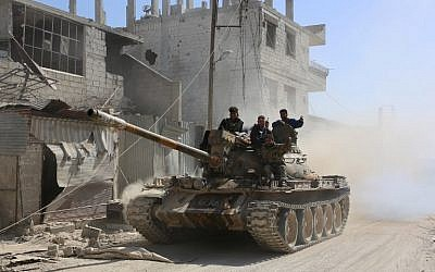 Syrian government forces deploy in the captured town of Beit Sawa it the Eastern Ghouta region on the outskirts of Damascus on March 14, 2018. (AFP/STRINGER)