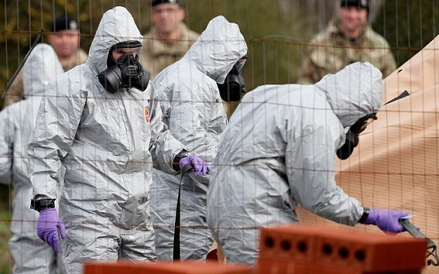 British military personnel wearing protective coveralls work to remove a vehicle connected to the March 4 nerve agent attack in Salisbury, from a residential street in Gillingham, southeast England, on March 14, 2018. (AFP Photo/Adrian Dennis)