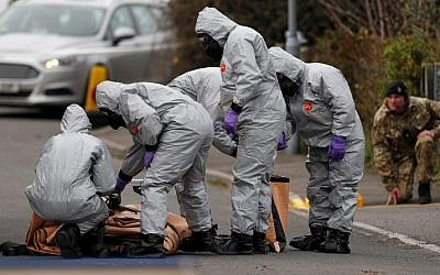 British Military personnel wearing protective coveralls work to remove a vehicle connected to the March 4 nerve agent attack in Salisbury, southeast England on March 14, 2018. (Adrian DENNIS/AFP)