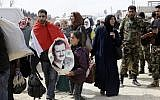 A Syrian man draped in the national flag walks with another girl carrying a poster of Syrian President Bashar al-Assad, as they walk with other civilians evacuated from the eastern Ghouta enclave, March 15, 2018. (LOUAI BESHARA/AFP)