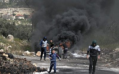 Palestinians burn tires during clashes with Israeli soldiers in the northern West Bank village of Kfar Qaddum on March 16, 2018. (AFP Photo/Jaafar Ashtiyeh)