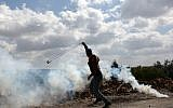 A young Palestinian protester prepares to fire a slingshot during clashes with Israeli soldiers in the village of Kfar Qaddum, near Nablus, in the West Bank, on March 16, 2018. (AFP PHOTO / JAAFAR ASHTIYEH)