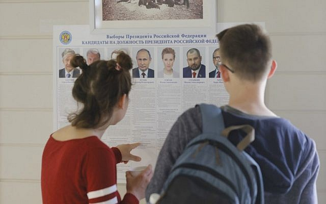 Russian nationals in Israel look at a list of candidates ahead of casting their ballots during the first round of the 2018 Russian presidential elections at the Sergei Compound in Jerusalem on March 18, 2018. (AFP Photo)