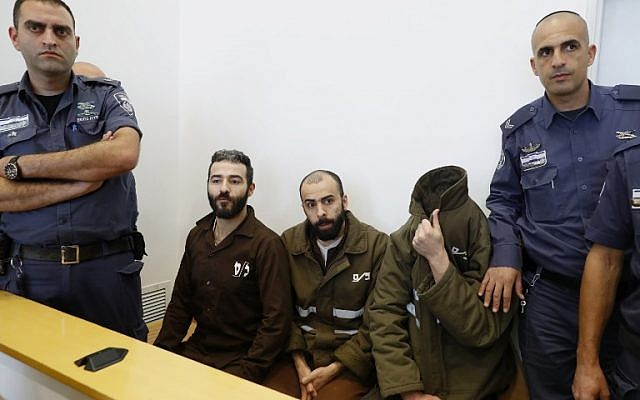 French national Romain Franck (R), 24, a worker at the French consulate, and Palestinian Moufak al-Ajluni (L) and Mohamed Katout (C) appear in court the southern Israeli city of Beersheba on March 19, 2018, to face charges of smuggling guns from Gaza. (AFP PHOTO / JACK GUEZ)