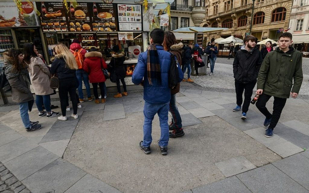 Tourists stand or walk across the pavement of the pedestrian zone at Wenceslas Square in Prague on March 15, 2018. (AFP PHOTO / Michal CIZEK)