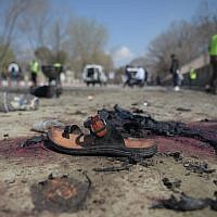 A sandal is seen laying on the ground along a road at the site of a suicide bombing attack in Kabul on March 21, 2018. (AFP PHOTO / SHAH MARAI)