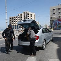 Illustrative: Hamas police inspect the trunk of a car at a checkpoint amid tightened security around Gaza city on March 22, 2018. (AFP/Mohammed Abed)