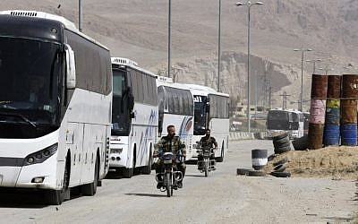 Syrian regime forces drive motorbikes past buses waiting at the entrance of Harasta in Eastern Ghouta, on the outskirts of Damascus, on March 22, 2018, after a deal was struck with the rebels in the area to evacuate the town. (AFP PHOTO / Louai Beshara)