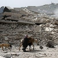 A picture taken on March 22, 2018 shows a man walking with a loaded donkey and followed by a dog past the rubble of a destroyed building in the northwestern Syrian city of Afrin. (AFP PHOTO / Nazeer al-Khatib)