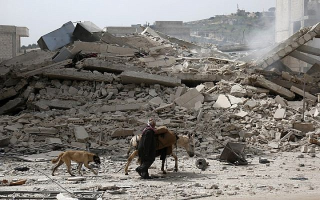 A picture taken on March 22, 2018, shows a man walking with a loaded donkey and followed by a dog past the rubble of a destroyed building in the northwestern Syrian city of Afrin. (AFP PHOTO / Nazeer al-Khatib)
