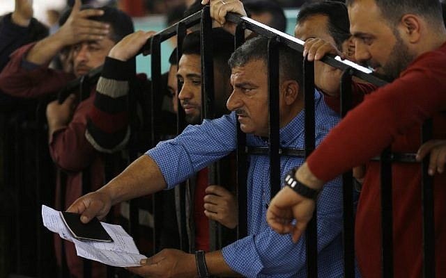 Palestinians wait for travel permits to cross into Egypt through the Rafah border crossing after it was opened by Egyptian authorities for humanitarian cases, in Khan Yunis in the southern Gaza Strip on March 23, 2018. (AFP/Mohammed Abed)