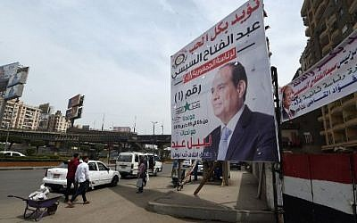 People walk by election campaign posters in support to the Egyptian President for the upcoming presidential election in central Cairo on March 23, 2018. Egyptians will vote for the presidential election in a March 26-28 poll. ( AFP PHOTO / FETHI BELAID)