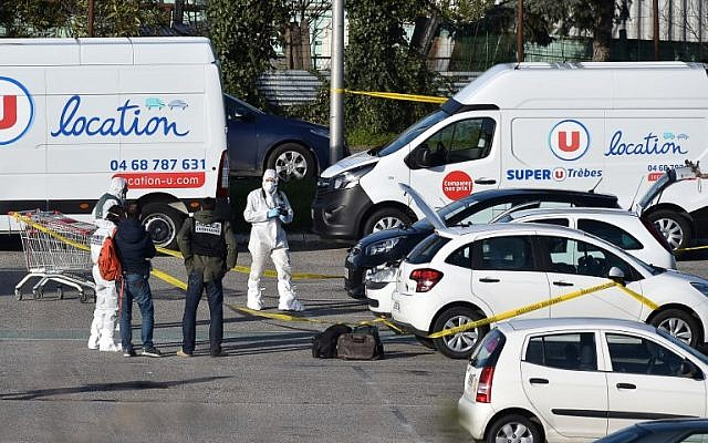 French forensic officers arrive to inspect a vehicle (center, hood up) believed to belong to terrorist Radouane Lakdim, and parked outside the Super U supermarket in the town of Trebes in southern France, where Lakdim carried out his attack, on March 23, 2018. (AFP Photo/Pascal Pavani)