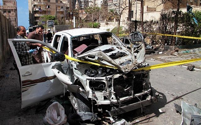 Egyptian forensics check a destroyed vehicle at the site of a bomb attack in the northern port city of Alexandria, which hit a convoy of the city's security chief, on March 24, 2018. (AFP PHOTO)