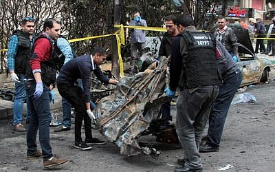 Egyptian forensics and security forces check the site of a bomb attack in the northern port city of Alexandria, which hit a convoy of the city's security chief, on March 24, 2018. (AFP PHOTO / STR)