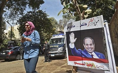 "An Egyptian woman walks past an electoral banner commissioned by a member of parliament depicting incumbent President Abdel-Fattah el-Sissi seen with a caption reading in Arabic ""for the sake of Egypt we will continue the story of a nation,"" outside a polling station in the capital Cairo's central neighborhood of Zamalek on March 26, 2018. (AFP PHOTO / KHALED DESOUKI)"