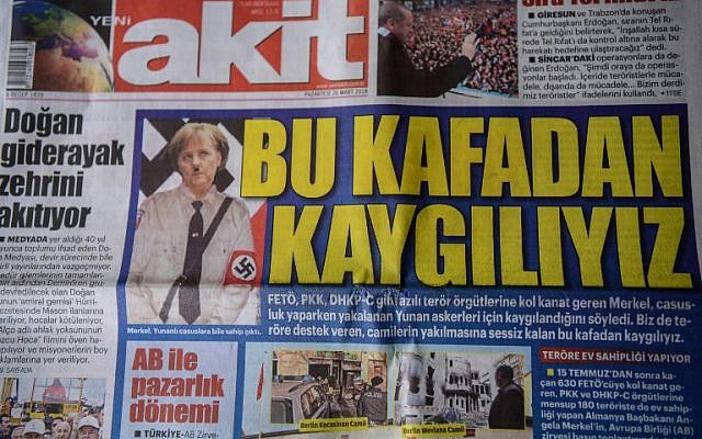 """A picture taken on March 26, 2018, in Istanbul shows the front page of the daily Yeni Akit depicting a doctored photo of German Chancellor Angela Merkel in a Nazi-uniform under the headline """"We are concerned by this mentality."""" (AFP Photo/Ozan Kose)"""