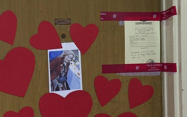 This AFP TV video frame grab shows a picture of Mireille Knoll, heart-shaped papers and police seals posted on the door of her apartment in Paris, March 27, 2018. (Laetitia PERON)