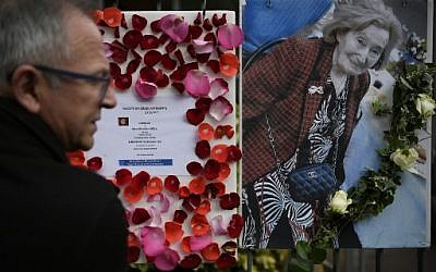 """A man stands in front of a picture of Mireille Knoll and a message announcing a """"Marche Blanche"""" condemning the alleged anti-Semitic motive for of her killing, placed on the fence surrounding her building in Paris on March 27, 2018, after she was found dead in her apartment on March 23 by firefighters called to extinguish a blaze. Two people have been charged with the murder of an 85-year-old French Jewish woman, who was stabbed and whose body was then set alight in a crime being treated as anti-Semitic, a judicial source said on March 27, 2018. ( AFP PHOTO / Lionel BONAVENTURE)"""