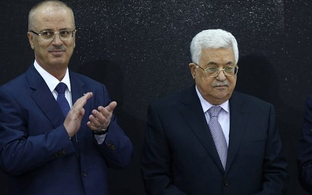 Palestinian Authority President Mahmoud Abbas, right, and Palestinian Prime Minister Rami Hamdallah attend the presentation of the preliminary results of the general census of population, housing and establishments, in Ramallah, in the West Bank on March 28, 2018. (AFP/Abbas Momani)