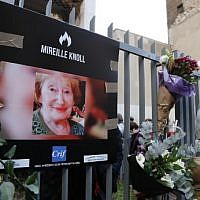A photograph of murdered Holocaust survivor Mireille Knoll is placed along with flowers on the fence surrounding her building in Paris on March 28, 2018. (Francois Guillot/AFP)