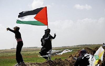 A Palestinian woman wearing niqab (full face veil) flashes the victory gesture while holding a Palestinian flag as others fly kites during a demonstration ahead of Land Day, at a tent city near the border with Israel east of Gaza City on March 29, 2018. (AFP PHOTO / MOHAMMED ABED)