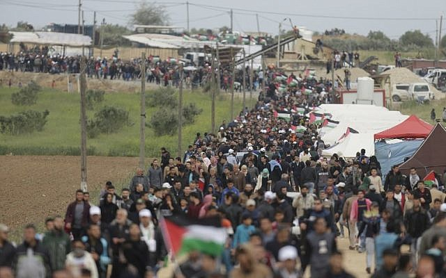 A picture taken on March 30, 2018 shows Palestinians marching past a tent city erected along the border with Israel east of Gaza City in the Gaza strip. (AFP/ MAHMUD HAMS)
