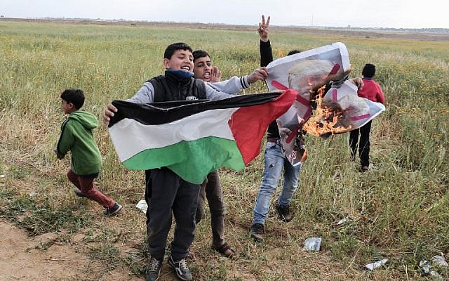 Palestinian children wave a Palestinian flag as they burn a crossed-out poster depicting US President Donald Trump, during a large protest near the southern Gaza city of Khan Younis on March 30, 2018. (Said Khatib/AFP)