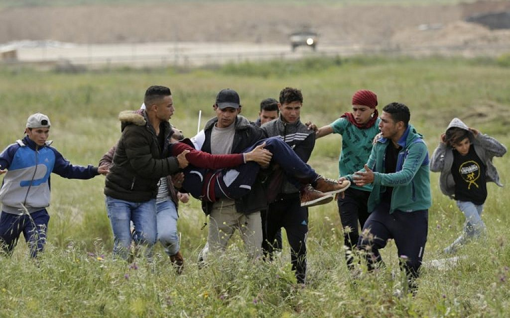 An injured Palestinian youth is carried by other protesters as they flee during clashes after a demonstration near the border with Israel east of Gaza City commemorating Land Day, March 30, 2018 (AFP/ MAHMUD HAMS)