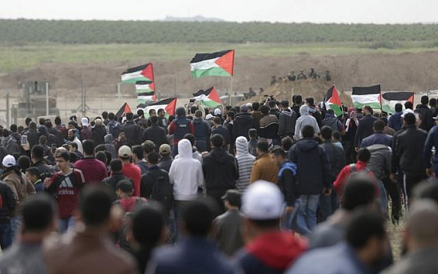 Palestinians march past a tent city erected along the border with Israel east of Gaza City in the Gaza strip to commemorate Land Day, March 30, 2018 (AFP PHOTO / MAHMUD HAMS)