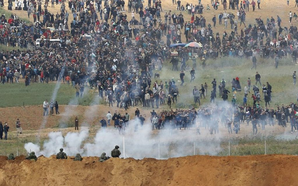 A picture taken on March 30, 2018 from the southern Israeli kibbutz of Nahal Oz across the border from the Gaza Strip shows tear gas grenades falling during a Palestinian protest, with Israeli soldiers seen below in the foreground. (AFP PHOTO / Jack GUEZ)