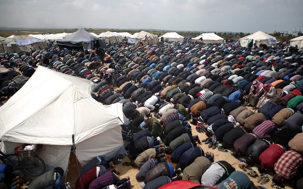 Muslim worshippers perform Friday noon prayers during a tent city protest near the border with Israel east of Jabalia on March 30, 2018. (AFP PHOTO / Mohammed ABED)
