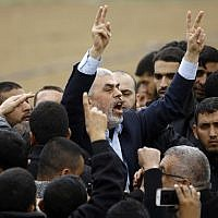 Islamist Hamas terror group leader Yihya Sinwar shouts slogans and flashes the victory gesture as he takes part in a protest near the border with Israel east of Jabaliya in the northern Gaza Strip on March 30, 2018. (AFP/ Mohammed ABED)