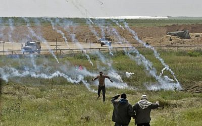 A picture taken on March 30, 2018 shows Palestinians fleeing as tear gas grenades begin to drop during a demonstration near the border with Israel east of Gaza City. (AFP/Mahmud Hams)