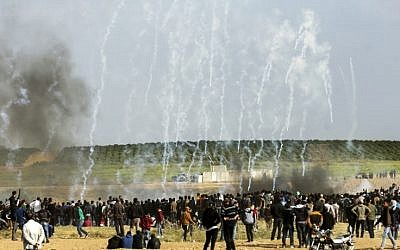 Palestinian protestors run for cover from tear gas fired by Israeli security forces during clashes following a demonstration commemorating Land Day, near the border with Israel, east of Gaza City, on March 30, 2018. (Mahmud Hams/AFP)