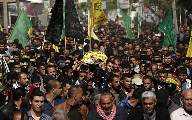 Palestinians carry the body of Hamdan Abu Amsha, said killed a day earlier by Israeli fire during a mass border protest along the security fence, in Beit Hanun in the northern of Gaza Strip on March 31, 2018. (AFP/ MAHMUD HAMS)