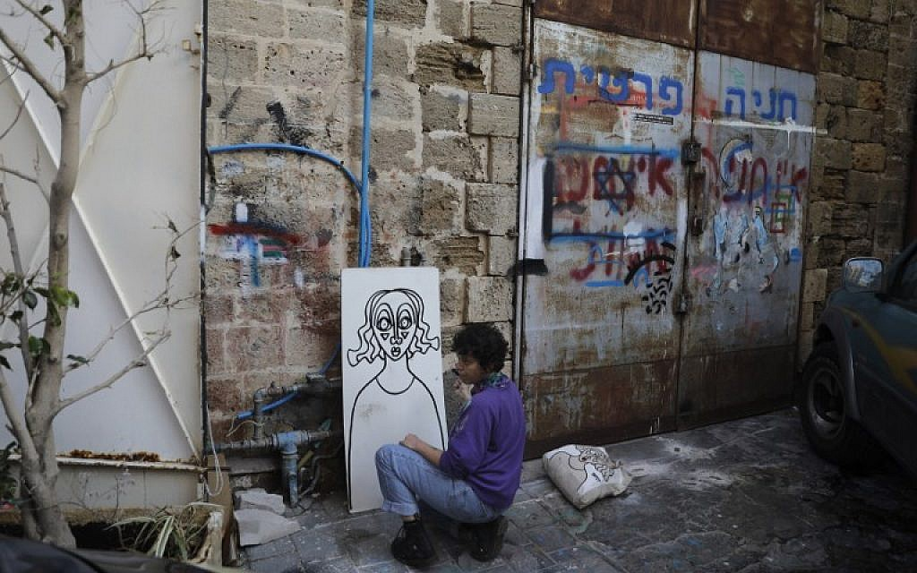 Israeli-born New York-based street artist Sara Erenthal draws one of her emblematic woman's faces in Tel Aviv on January 28, 2018. (AFP Photo/Menahem Kahana)