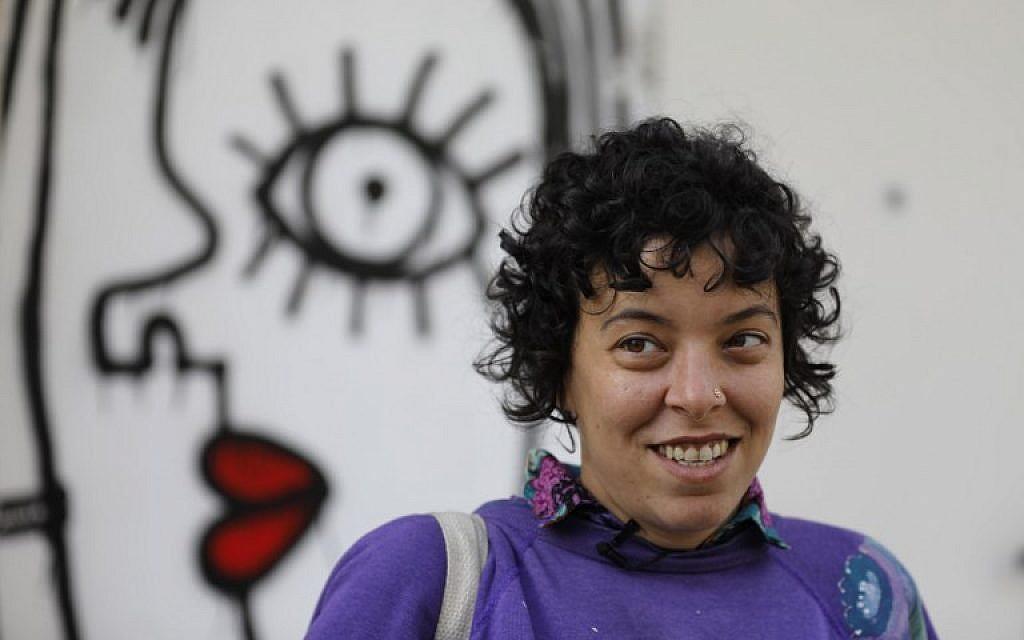 Israeli-born New York-based street artist Sara Erenthal smiles in front of one of her murals in Tel Aviv on January 28, 2018. (AFP Photo/Menahem Kahana)