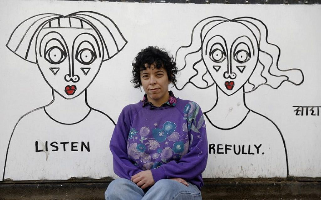 Israeli-born New York-based street artist Sara Erenthal sits in front of one of her murals in Tel Aviv on January 28, 2018. (AFP Photo/Menahem Kahana)