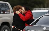 Vanessa Flores (R) embraces another woman after she leaves the locked down Veterans Home of California during an active shooter turned hostage situation on March 9, 2018, in Yountville, California. (Stephen Lam/Getty Images/AFP)