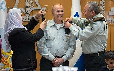 Kamil Abu Rokon, center, Israel's next liaison to the Palestinians, receives the rank of major general from IDF Chief of Staff Gadi Eisenkot, right, and Abu Rokon's wife in a ceremony at the army's Tel Aviv headquarters on March 29, 2018. (Israel Defense Forces)