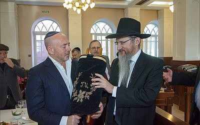 Russian chief rabbi Berel Lazar, right, with Baruch Ramatsky, holding the Torah scroll Ramatsky's family has kept hidden for the last 90 years, inside the synagogue of Tomsk, February 1, 2018. (Courtesy Chabad of Tomsk)
