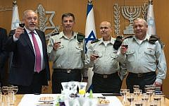 From left, Defense Minister Avigdor Liberman, outgoing liaison to the Palestinians Maj. Gen. Yoav MordechaiI, incoming liaison to the Palestinians, Maj. Gen. Kamil Abu Rokon, and IDF Chief of Staff Gadi Eisenkot raise a toast during a ceremony at the army's Tel Aviv headquarters on March 29, 2018. (Israel Defense Forces)