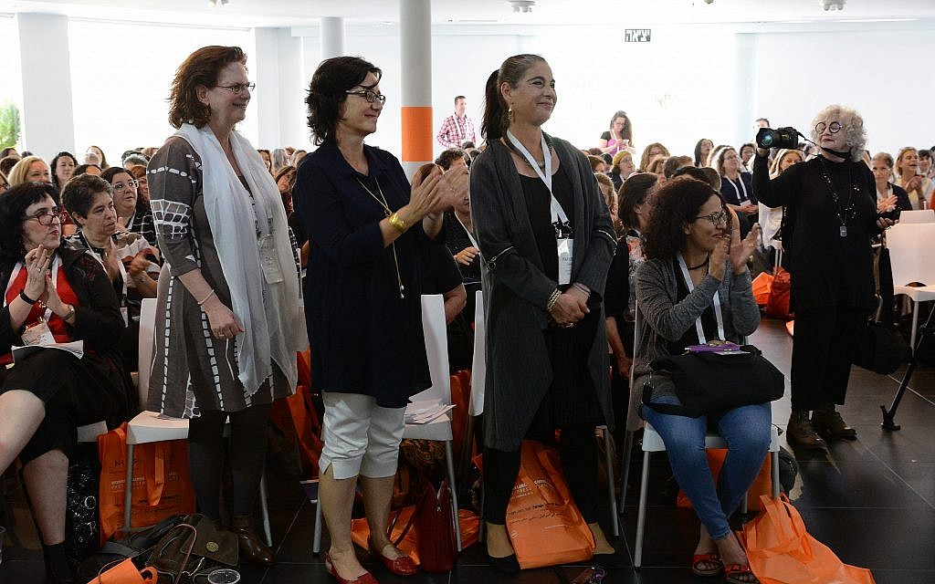 Hamutal Gouri, executive director of The Dafna Fund, and other attendees stand to cheer during the NCJW symposium's opening session. (Gal Mosenson)
