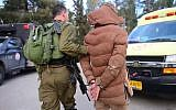 An Israeli soldier arresting a suspect after a raid in the West Bank city of Nablus, on March 18, 2018. (IDF Spokesperson)