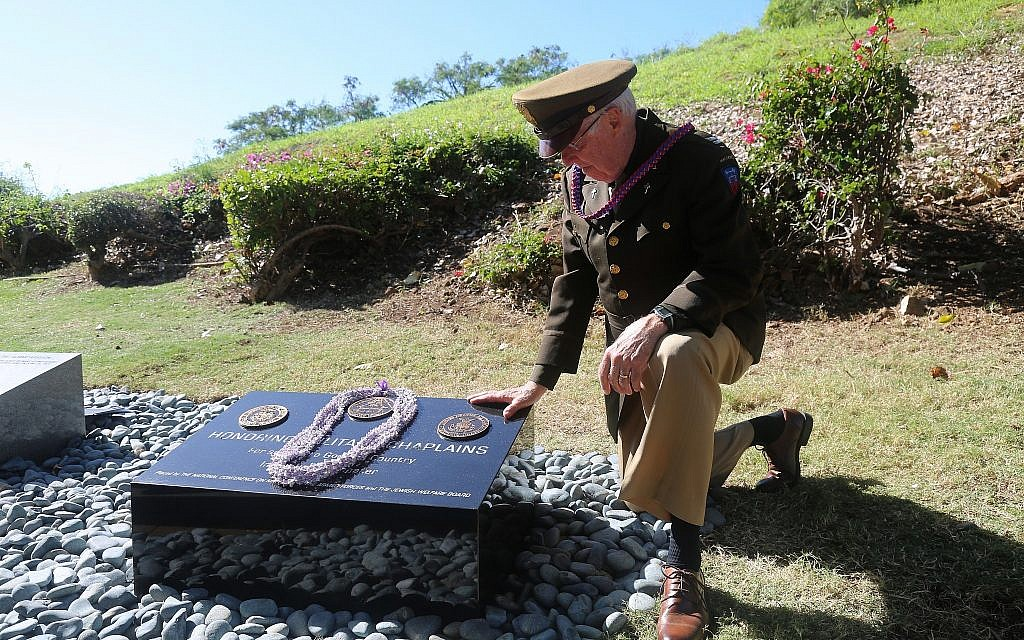 Chaplain Dick Stenbakken kneels by the Chaplains Memorial at the Punchbowl Cemetery. (Courtesy)