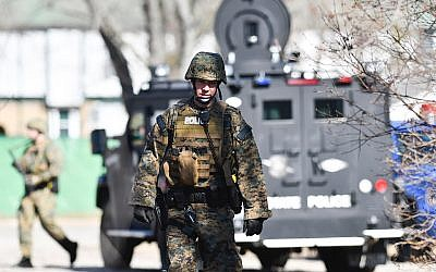 Law enforcement officers search a wooded area for a suspect involved in a shooting at a Central Michigan University residence hall on Friday, March 2, 2018 in Mt. Pleasant, Mich.  (Matthew Dae Smith/Lansing State Journal via AP)