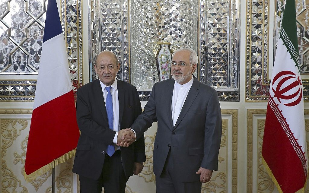 Iranian Foreign Minister Mohammad Javad Zarif, right, and his French counterpart Jean-Yves Le Drian, shake hands for journalists at the start of their meeting in Tehran, Iran, on March 5, 2018. (AP Photo/Vahid Salemi)