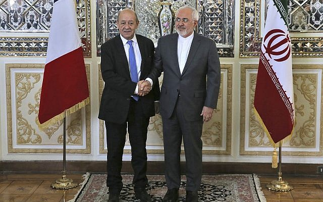 Iranian Foreign Minister Mohammad Javad Zarif, right, and his French counterpart Jean-Yves Le Drian, shake hands for journalists at the start of their meeting in Tehran, Iran on, March 5, 2018. (AP Photo/Vahid Salemi)