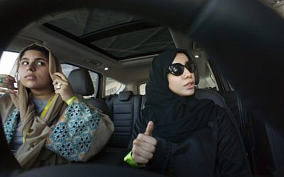 Fatima Salem, right, giggles as Sara Ghouth adjusts her veil, during training sponsored by Ford Motor, in Jiddah, Saudi Arabia, March 6, 2018. (AP Photo/Amr Nabil)